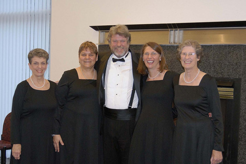 "The Falls Church contingent of the New Dominion Chorale models new concert garb, smart black dresses for women replacing the white blouse/black skirt costume.No change in the men's dress. From left, Beverly Laub, Rosemarie Hunziker, James Oglethorpe, Renee Andrews, Jennifer Heffernan, all of Falls Church. The Chorale's holiday concert, featuring Bach's ""Magnificat,"" Conductor Thomas Beveridge's new ""Magnificat"" and singalong carols, takes place at  4:00 pm, Sunday, Dec. 3, at the Schlesinger Center in Alexandria. Tickets are $25; $20 for seniors; $5 for students; and $20 for group sales. Free parking. Purchase tickets online at www.newdominion.org; by phone, 703-442-9404; or in person at Foxes Music, Falls Church, or Maley's McLean Music, McLean."