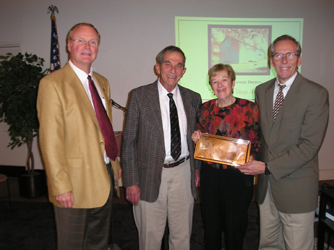 BARRY BUSCHOW (LEFT) and Keith Thurston (right) present the Village Preservation Society's Virginia Village Award to George and Joan Burgess at the VPIS Annual Meeting on Nov. 9. The award was given in appreciation for the Burgess's dedication to improving the quality of live in Falls Church through historic preservation, enhancement and interpretation of Cherry Hill Farm.