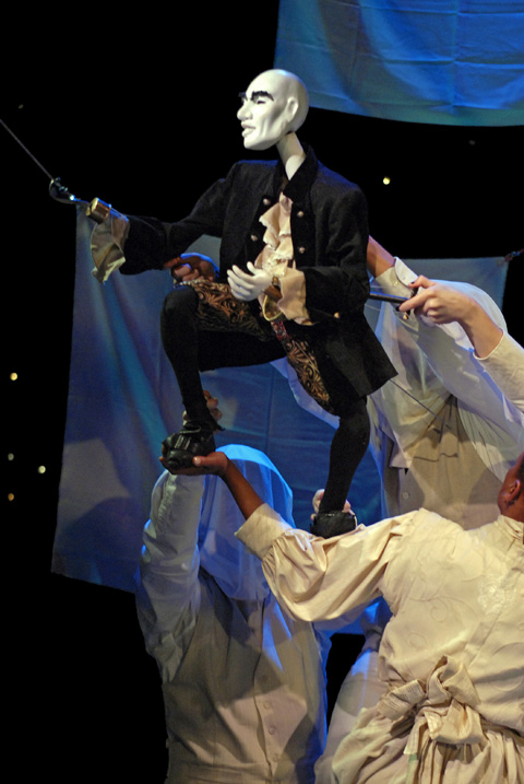 """Hook strikes a """"classy"""" pose with help from the Mabou Mines Bunraku puppeteers and The Narrator Karen Kandel in Arena Stage's presentation of """"Peter & Wendy."""" (Photo courtesy: Arena Stage)"""