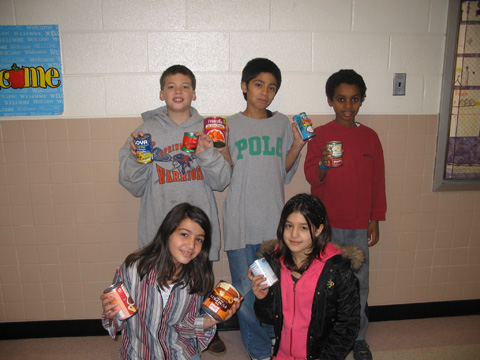 Students at Springfield Estates Elementary School proudly show off some of the food they have collected during the schoolwide food drive, organized by counselor Carolyn Gibson, which will be distributed to local needy families and individuals. (Photo: Courtesy Leann Kniller)